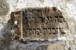 Sasha pulled the new recovered matzevah fragment free from winter ice