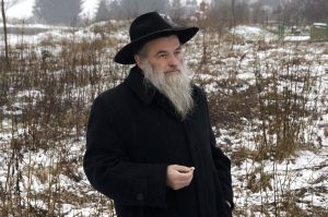 Rabbi Kolesnyk holds a flower while listening