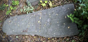 An intact but uprooted headstone in the cemetery