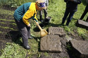 Rohatyn residents, volunteers, supporters, and advisors clean Jewish headstones recovered in a garden before transport to the old Jewish cemetery